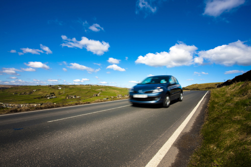 A car speeds by on a country road.