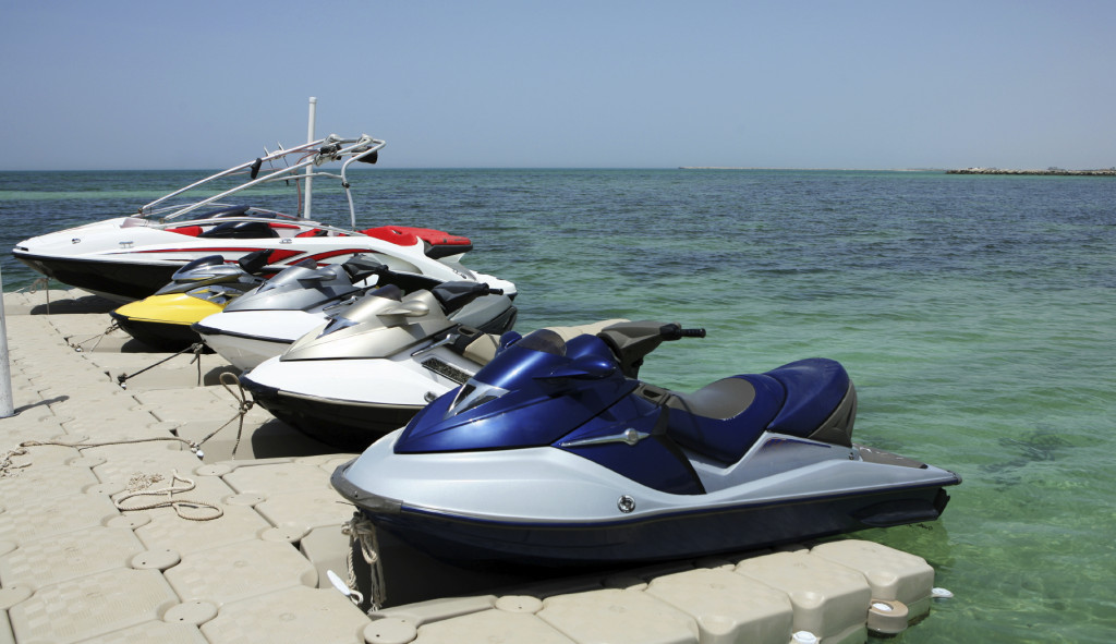 Jet skis and a speedboat, tied up in a marina.
